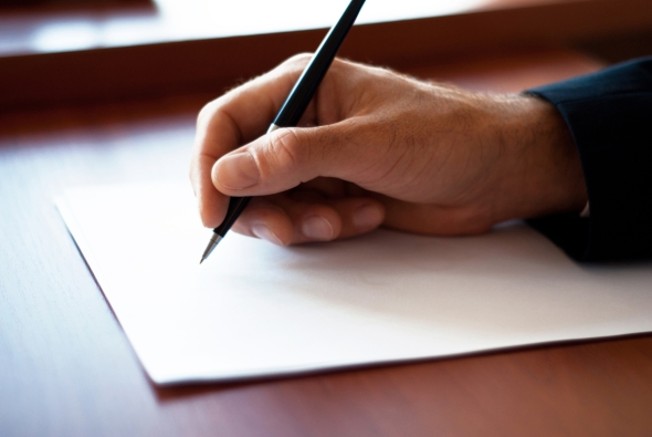Man writing on the paper in the office
